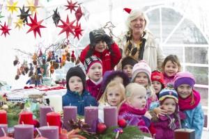 Ingrid Dahmen im Kreis ihrer Schützlinge und umgeben von zahlreichen Weihnachtsbasteleien, die zum Jubiläum verkauft wurden. Bild: Tameer Gunnar Eden/Eifeler Presse Agentur/epa