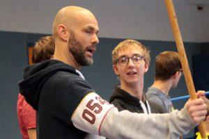 Martijn Theisen achtet darauf, dass die Schüler sich bei der Kampfchoreografie nicht verletzen und zeigt ihnen, wie man die Schwerter (noch sind es Holzstäbe) richtig handhabt. Bild: Michael Thalken/Eifeler Presse Agentur/epa